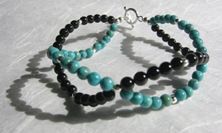 Handcrafted turquoise and black onyx bracelet with sterling silver toggle clasp.